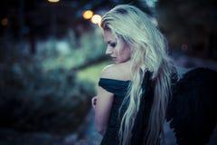 Sexy blonder Engel, junge Frau mit schwarzen Flügeln, Herbstszene Lizenzfreies Stockbild