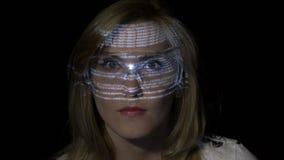 Sexy blonder Hackermädchen-Leseprogrammiercode im Raum der virtuellen Realität, während die Datenzeichen auf ihrem Gesicht projek stock footage