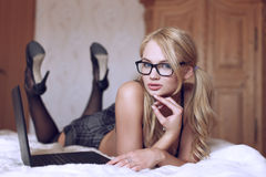 Sexy blonder Student, der auf Bett mit Laptop aufwirft Lizenzfreie Stockbilder