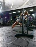 Sexy blonder Trainer, der in der Sportturnhalle aufwirft Stockbild