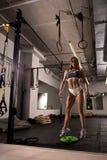Sexy blonder Trainer, der in der Sportturnhalle aufwirft Stockbilder