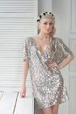 Sexy blondes im silbernen Kleid und glänzend, mit einem Kranz auf ihrem Haar Lizenzfreie Stockbilder