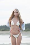 sexy blondes Mädchen auf dem Strand mit Palmen und blauem Himmel Stockfoto