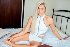 Sexy blondes Mädchen, das auf dem Schlechten und dem Denken sitzt Lizenzfreie Stockfotografie