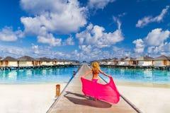 Sexy blondes Mädchen, das auf den Strand mit einem rosa Strandschal geht Luxusstrandlandhäuser und hölzerne Pierbahn Lizenzfreies Stockfoto