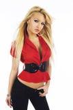 Sexy blondes Mädchen in der roten Bluse mit schwarzem Gürtel auf weißem Hintergrund Lizenzfreie Stockfotografie