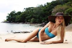 Sexy blondes Mädchen im Bikini und in elegantem Hut, die auf tropischem Strand sich entspannen Lizenzfreie Stockfotografie