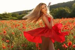 Sexy blondes Mädchen im eleganten Kleid, das auf dem Sommergebiet von roten Mohnblumen aufwirft Lizenzfreie Stockbilder