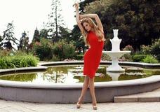 Sexy blondes Mädchen im eleganten Kleid, das im Sommerpark aufwirft Lizenzfreie Stockfotos