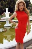 Sexy blondes Mädchen im eleganten Kleid, das im Sommerpark aufwirft Stockfotografie