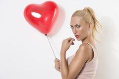 Sexy blondes Mädchen mit Ballon und der Hand nahe dem Mund Stockfotos