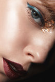 Sexy blondes Mädchen mit den roten Lippen und Gold auf den Augen in einem dunklen Mantel lizenzfreies stockfoto