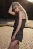 Sexy blondes Modell im schwarzen Spielanzug, der im Park in sonnigem DA aufwirft Stockfotos