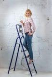 Sexy blondes Modell mit der beleuchteten Laterne, die auf Stehleiter steht Lizenzfreies Stockbild
