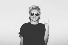 Sexy blondes schlechtes Mädchen der stilvollen Mode in einem schwarzen T-Shirt und in der Felsensonnenbrille Gefährliche felsige  Lizenzfreies Stockbild