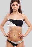 Sexy blondevrouw die het swimwear stellen op kleurenachtergrond dragen Perfect Lichaam Bikinicatalogus Stock Afbeelding