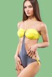 Sexy blondevrouw die het swimwear stellen op kleurenachtergrond dragen Perfect Lichaam Bikinicatalogus Stock Foto