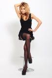 Sexy blondevrouw in elegante zwarte kleding Stock Foto's