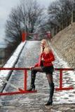 Sexy blondevrouw in rood leerjasje en minirok Royalty-vrije Stock Afbeelding