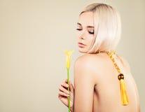 Sexy Blondie-Modell Woman Nettes Gesicht, gelbe Blume, blondes Haar Stockbild