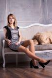 Sexy Blondine auf einem Sofa Lizenzfreie Stockfotografie