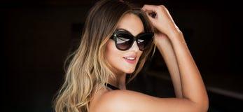 Sexy Blondine bei der Sonnenbrilleaufstellung lizenzfreies stockfoto