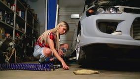 Sexy Blondine in den Reparaturen einer Garage ein Auto stock footage