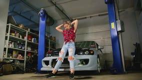Sexy Blondine in den Reparaturen einer Garage ein Auto stock video