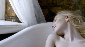 Sexy Blondine des sch?nen M?dchens morgens, die im Badezimmer aufwirft t?tigkeit Junge Blondine, die im Bad in liegen stockbilder