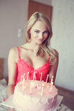 Sexy Blondine, die Geburtstagskuchen in der Unterwäsche halten Stockbild