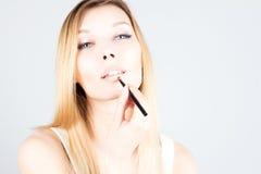 Sexy Blondine, die Lippenstift auf Lippen anwenden Bilden Sie Künstler Lizenzfreie Stockfotografie