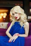 Sexy Blondine im blauen Kleid, das in einem Stuhl im Restaurant sitzt Stockfotos
