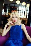 Sexy Blondine im blauen Kleid, das in einem Stuhl im Restaurant sitzt Stockfoto