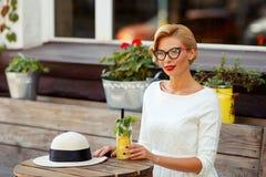 Sexy Blondine im Retro- Blick, der im Café stillsteht Lizenzfreies Stockbild