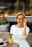 Sexy Blondine im Retro- Blick, der im Café stillsteht Lizenzfreie Stockbilder