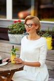 Sexy Blondine im Retro- Blick, der im Café stillsteht Stockbilder