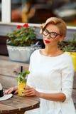 Sexy Blondine im Retro- Blick, der im Café stillsteht Stockfotografie