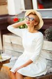 Sexy Blondine im Retro- Blick, der im Café stillsteht Stockfoto