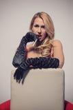 Sexy Blondine im roten Kleid, das auf Stuhl mit Zigarette sitzt Stockfoto
