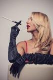 Sexy Blondine im roten Kleid, das auf Stuhl mit Zigarette sitzt Stockbild