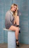 Sexy Blondine mit den langen Beinen auf einem Hintergrund von blauen Schirmen Lizenzfreie Stockfotos