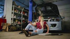 Sexy Blondine raucht am Auto in der Garage stock footage