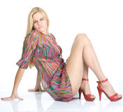 Sexy blondy on high red heels sitting on floor Royalty Free Stock Photos