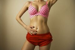 Sexy body in polka dot bra and red pants, contrast lightning Royalty Free Stock Photography