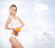Sexy body of a young and fit woman holding a fresh orange Stock Images