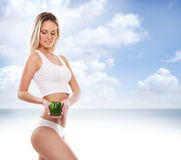 Sexy body of a young and fit woman holding a fresh paprika Stock Image
