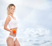 Sexy body of a young and fit woman holding a fresh paprika Royalty Free Stock Photo