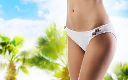Sexy body of a young and fit woman on a resort background Royalty Free Stock Photography