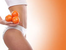 Sexy body of a young and fit woman in a white lingerie holding tomatoes Royalty Free Stock Image