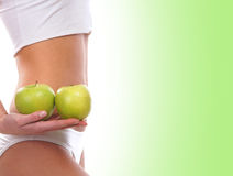 Sexy body of a young woman holding green apples Stock Photos
